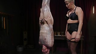 Milf mistress paddles man wrapped in plastic